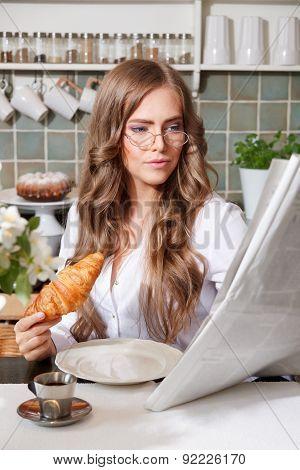 Woman Reading Newspaper While Having Breakfast