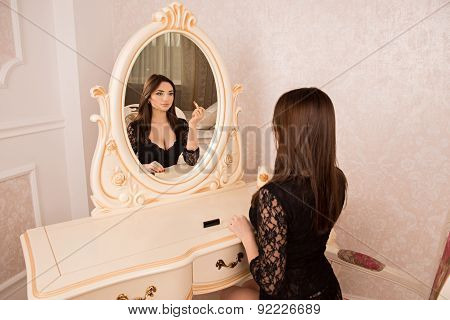 Sexy Girl Sitting At A Mirror And Paints Her Lips Lipstick