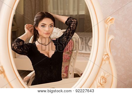Beautiful Girl Sitting Near A Mirror And Dress Necklace On Her Neck..