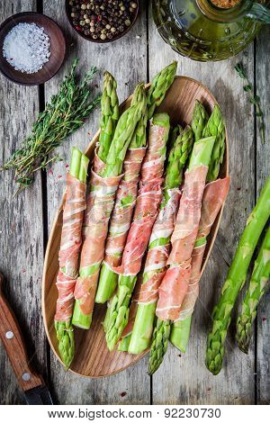Fresh Organic Asparagus Wrapped In Prosciutto On A bowl