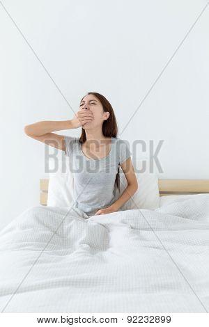 Young woman sitting on bed, stretching arms above head and yawning