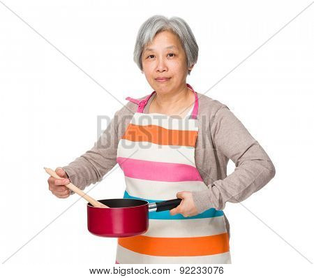 Elderly housewife using saucepan and wooden ladle