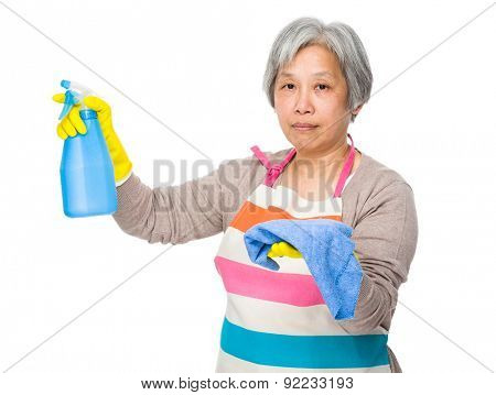 Elderly housewife hold with bottle spray and rag