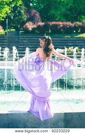 beautiful playful woman in fluttering lavender elegant dress in front fountain, full body shot