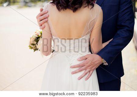 Groom in blue suit  holding brides back