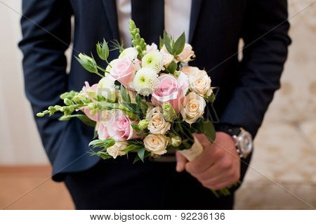Beautiful wedding colorful nosegay in grooms hands