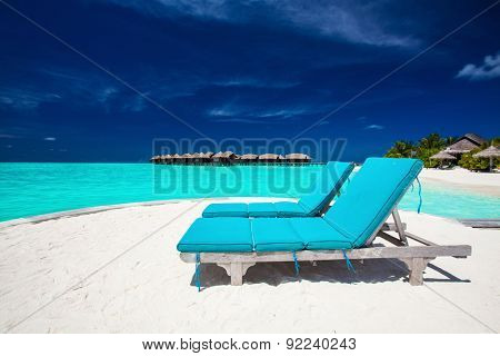 Two blue chairs on sandy island overlooking stunning tropical beach of Maldives