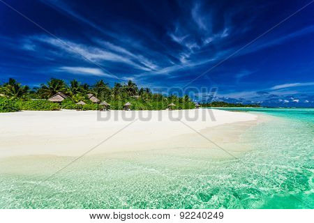 Palm trees over stunning lagoon and white sandy beach in Maldives