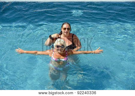 Women Are Doing Spa Exercises In Water Of Swimming Pool.