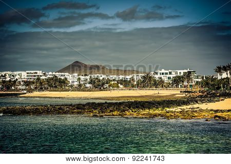 desert Lanzarote coast with a township on the background, Canary Islands, Spain