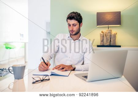 Handsome young smiling businessman working from home with a laptop with his coffee mug