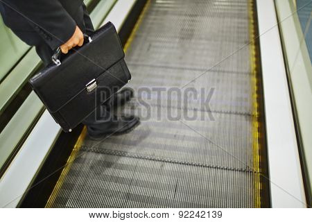 Close-up of legs of businessman with briefcase descending on escalator