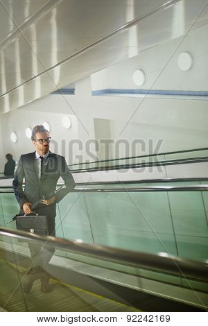 Serious businessman standing on ascending escalator