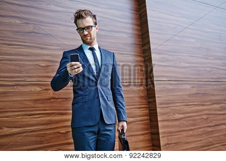 Businessman with briefcase and cellphone writing or reading sms