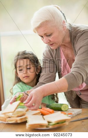 Girl looking at grandmother preparing sandwiches at home