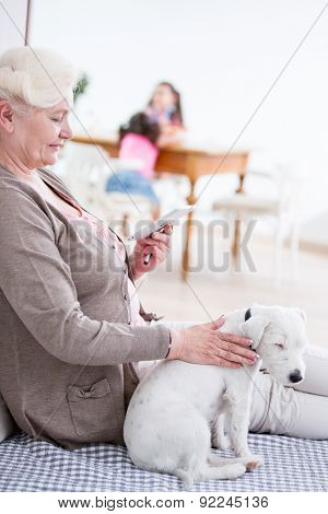 Side view of senior woman using digital tablet by dog at home