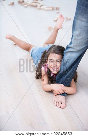 Portrait of happy girl being dragged by father on hardwood floor