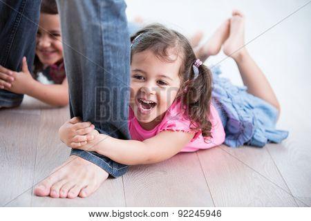 Playful girls holding father's legs on hardwood floor