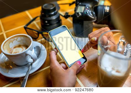 Photographer using mobile phone in the cafe