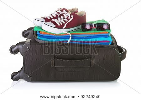 Ordinary Wheeled Black Suitcase Packed With Bright Summer Clothes and Sneakers