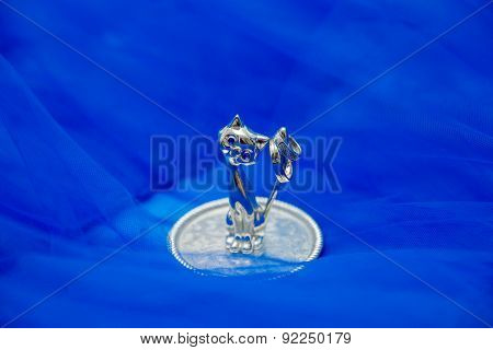 crystal figurines cat with rings on a plate on blue background