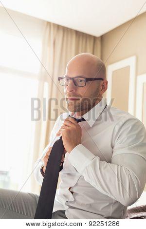 Mid adult businessman adjusting necktie at home