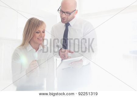 Happy mid adult business couple using tablet PC at home