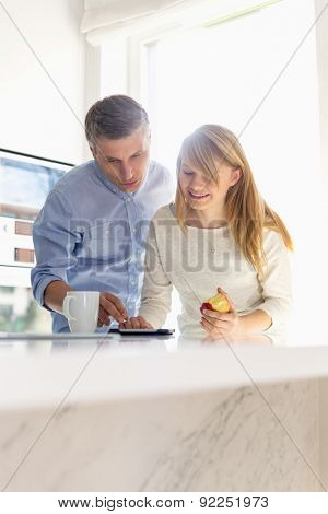 Father and daughter using tablet PC at home