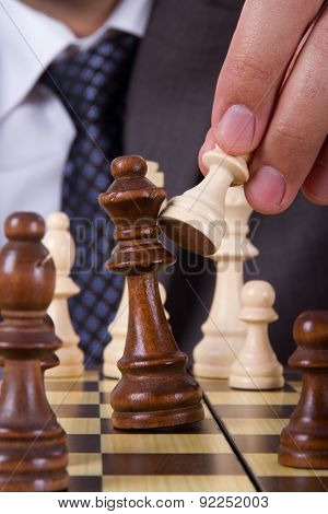 Businessman Holding Pawn Against King