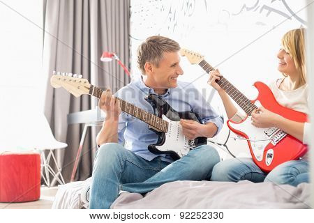 Happy father and daughter playing guitars at home