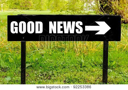 Good News Written On Directional Black Metal Sign