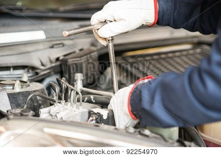 Closeup of an auto mechanic working on a car engine
