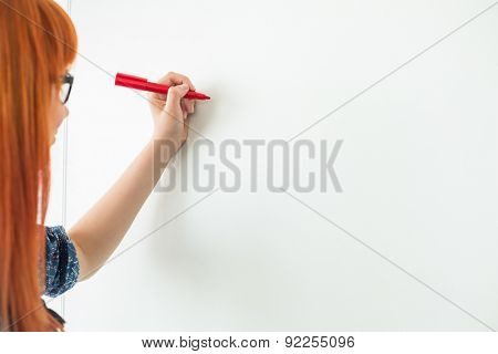 Cropped image of businesswomen writing on whiteboard in creative office