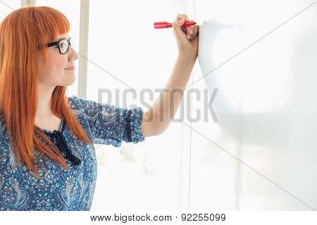 Smiling businesswomen writing on whiteboard in creative office