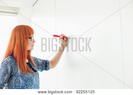 Businesswomen writing on whiteboard in creative office