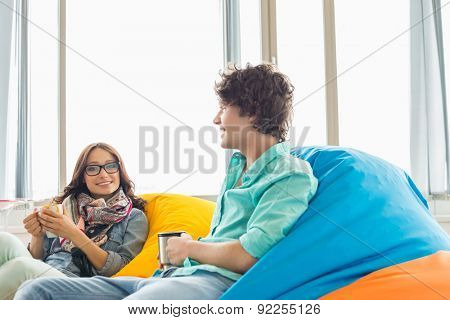 Business colleagues having coffee while relaxing on beanbag chairs in creative office