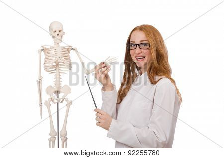 Young female doctor with skeleton isolated on white