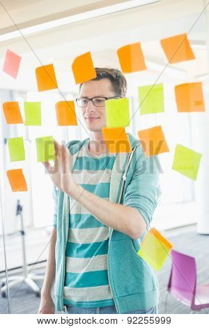 Smiling businessman reading sticky notes on glass wall in creative office