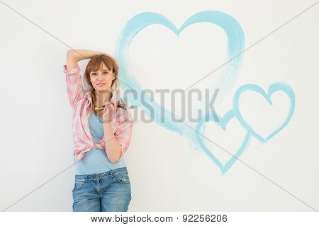 Portrait of beautiful woman holding paint brush with hearts painted on wall