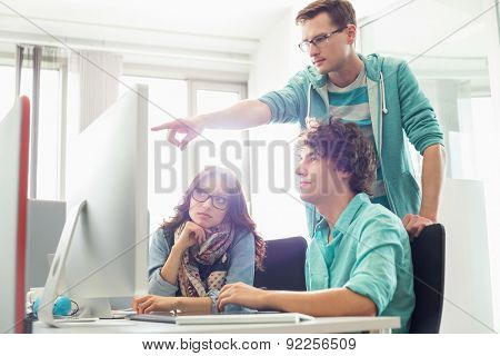 Businessman showing something to colleagues on computer in creative office