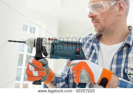 Mid-adult man drilling hole in wall