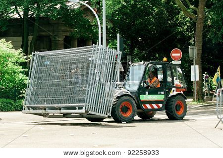 Tractor Carrying Metallic Fence On Urban Street