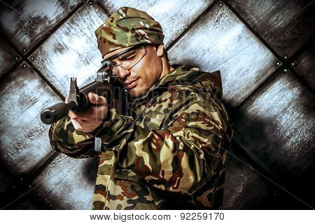 Brave soldier in camouflage holding automatic rifle. Military.