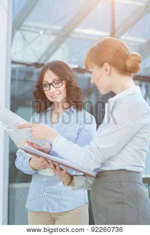 Businesswoman showing document to colleague in office