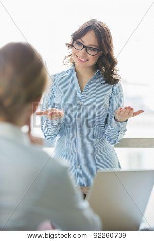 Happy businesswoman talking to businesswoman in office