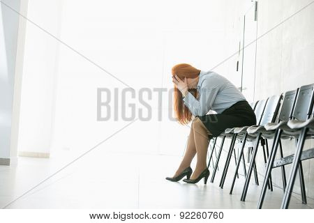 Side view of exhausted businesswoman sitting on chair in office