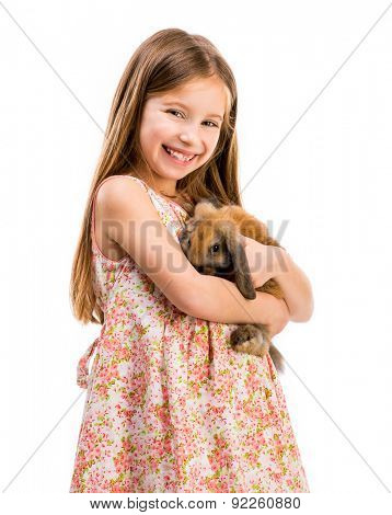 cute smiling girl in a summer dress with a baby rabbit on white