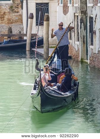 Venetian Gondolas With Tourist Sail In The Canal In Venice