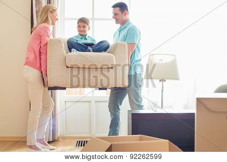 Parents carrying son on armchair in new house