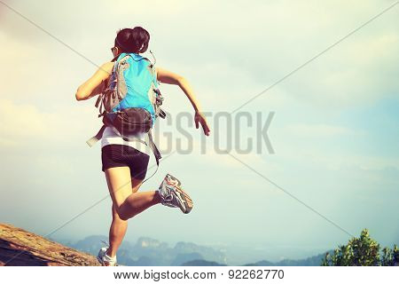 young asian woman hiker running on mountain peak cliff